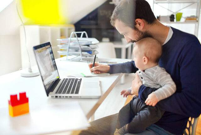 father working at home with baby care